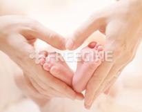 Tiny Newborn Baby`s feet on female Heart Shaped hands closeup