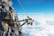 Businessman climbing on mountain with rope