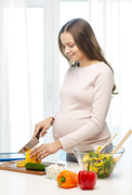 pregnancy, cooking food, healthy lifestyle, people and expectation concept - happy pregnant woman with knife chopping cucumber and preparing vegetable salad at home