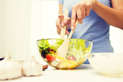 healthy eating, vegetarian food, dieting and people concept - close up of young woman cooking vegetable salad at home