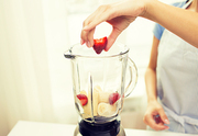 healthy eating, cooking, vegetarian food, diet and people concept - close up of woman with blender making banana strawberry fruit shake at home