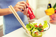 healthy eating, vegetarian food, cooking and people concept - close up of young woman seasoning vegetable salad with salt or pepper at home
