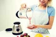 healthy eating, cooking, vegetarian food, dieting and people concept - close up of young woman pouring fruit shake from blender shaker jug to glass at home