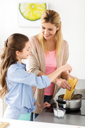 food, family and people concept - happy mother and daughter cooking and boiling spaghetti pasta for dinner at home kitchen