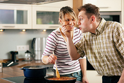 Couple cooking together in their kitchen the man tasting the sauce finding it very hot and spicy - as you can tell by his facial expression
