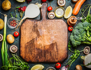 Fresh vegetables and  ingredients for cooking around vintage cutting board on rustic background, top view, place for text.  Vegan food , vegetarian and healthily cooking concept.