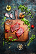 Delicious  beef steak on vintage cutting board with fresh various ingredients for tasty cooking on rustic wooden background, top view.