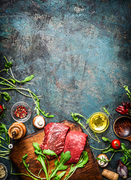 Beef steak and various ingredients for cooking on rustic wooden background, top view, frame.  Healthy, diet food concept.