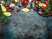 Fresh mussels with ingredients for cooking on rustic background, top view, border. Seafood concept