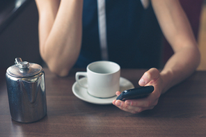A young woman is having a cup of coffee in a diner and is using her smartphone