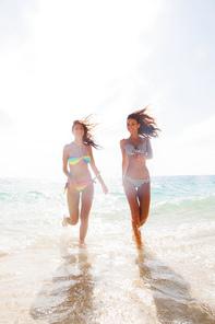 Young woman in bikini laying by tropical sea