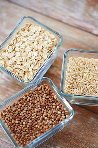 food, agriculture, cereals and healthy eating concept - close up of buckwheat, oatmeal and rice grain on wooden table