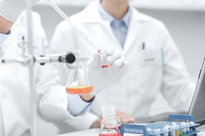 science, chemistry, technology, biology and people concept - close up of scientists hands with pipette filling test tube making research in clinical laboratory