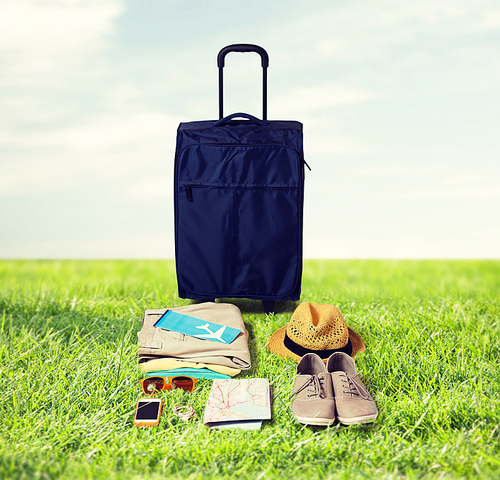 summer vacation, tourism and objects concept - travel bag, map, air ticket and clothes with personal stuff over blue sky and grass background