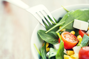 healthy eating, dieting, vegetarian kitchen and cooking concept - close up of vegetable salad bowl and fork at home