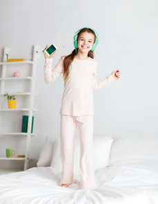 people, children, pajama party and technology concept - happy smiling girl in headphones with smartphone and listening to music at home