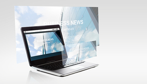 technology and mass media concept - laptop computer with business news on screen