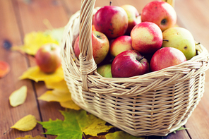 gardening, season, autumn and fruits concept - close up of wicker basket with ripe red apples and herbs on wooden table