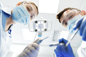 people, medicine, stomatology and health care concept - female dentist with dental mirror and probe checking up male patient teeth at dental clinic office
