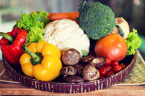 cooking, kitchen, vegetarian and food concept - basket of of fresh ripe juicy vegetables and mushrooms at kitchen or home