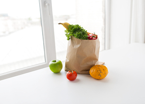 cooking, diet, vegetarian food and healthy eating concept - close up of paper bag with fresh ripe juicy vegetables, greens and fruits on kitchen table at home