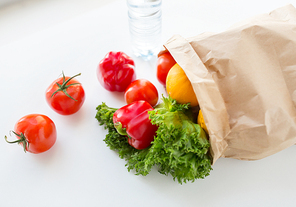 cooking, diet, vegetarian food and healthy eating concept - close up of paper bag with fresh ripe juicy vegetables and greens on kitchen table at home
