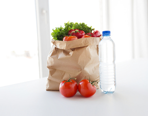 cooking, diet, vegetarian food and healthy eating concept - close up of paper bag with fresh ripe juicy vegetables and water bottle on kitchen table at home
