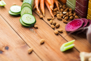 healthy eating, food, cooking, diet and vegetarian concept - different vegetables and almond nuts on wooden table