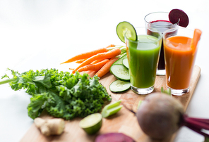 healthy eating, drinks, diet and detox concept - glasses with vegetable fresh juices and food on table