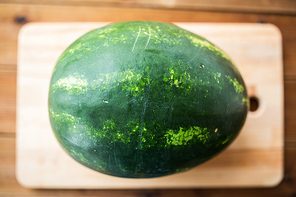 healthy eating, food, fruits and vegetarian concept - close up of watermelon on wooden cutting board