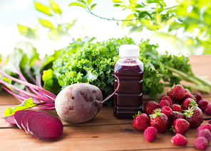 healthy eating, food, dieting and vegetarian concept - bottle with beetroot juice, fruits and vegetables on wooden table over green natural background