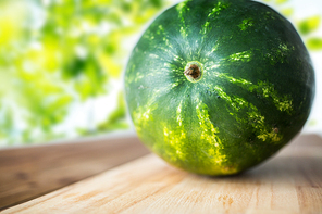 healthy eating, food, fruits and vegetarian concept - close up of watermelon on wooden cutting board over green natural background