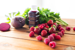 healthy eating, food, dieting and vegetarian concept - close up of bottle with beetroot juice, fruits and vegetables on wooden table