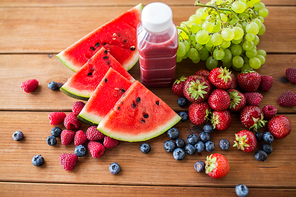healthy eating, food, dieting and vegetarian concept - bottle with fruit and berry juice or smoothie on wooden table
