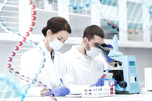 science, chemistry, technology, biology and people concept - young scientists with test tube and microscope making research in clinical laboratory and taking notes over dna molecule structure