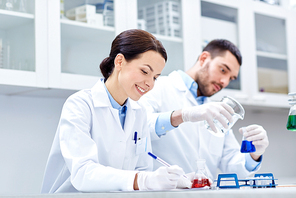 science, chemistry, biology, pharmacy and people concept - young scientists with pipette and flask making test or research in clinical laboratory