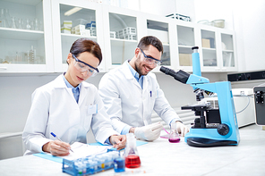 science, chemistry, technology, biology and people concept - young scientists shaking glass with reagent and making test or research in clinical laboratory