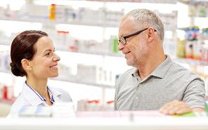 medicine, pharmaceutics, health care and people concept - happy pharmacist talking to senior man customer at drugstore