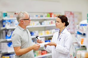 medicine, pharmaceutics, health care and people concept - pharmacist giving drug to senior man customer and taking prescription at drugstore
