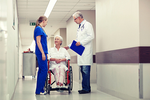 medicine, age, health care and people concept - doctor, nurse and senior woman patient in wheelchair at hospital corridor