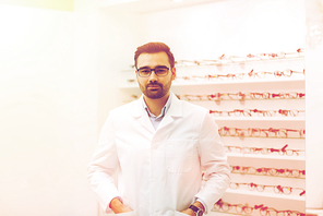 health care, people, eyesight and vision concept - man optician in glasses and white coat at optics store