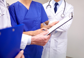 clinic, profession, people, healthcare and medicine concept - close up of doctors with clipboard at hospital
