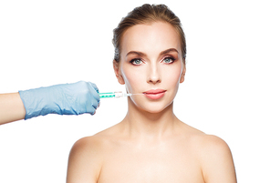 people, cosmetology, plastic surgery and beauty concept - beautiful young woman face and syringe making injection for lips augmentation over white background