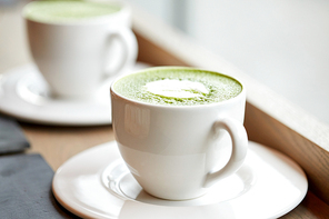 drink, diet, weight-loss and slimming concept - white cup of matcha green tea latte on table at restaurant or cafe