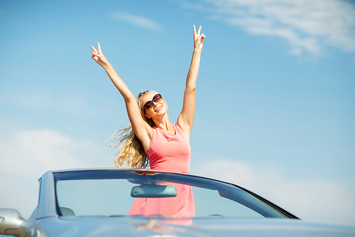 travel, summer holidays, road trip and people concept - happy young woman wearing sunglasses in convertible car enjoying sun