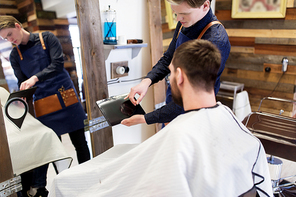 grooming, hairdressing and people concept - man and barber styling hair at barbershop