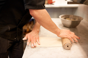 food, italian kitchen and cooking concept - cook hands with cutter cutting pizza to pieces at pizzeria