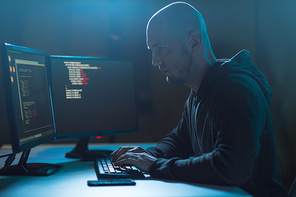 cybercrime, hacking and technology concept - male hacker in dark room writing code or using computer virus program for cyber attack