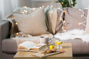 hygge and cozy home concept - oatmeal cookies, book, tea and lemon on wooden table in living room