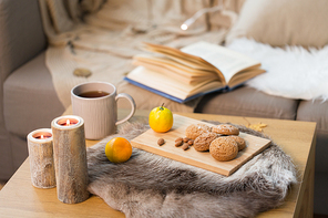 hygge and cozy home concept - oatmeal cookies, lemon tea and candles on wooden table in living room